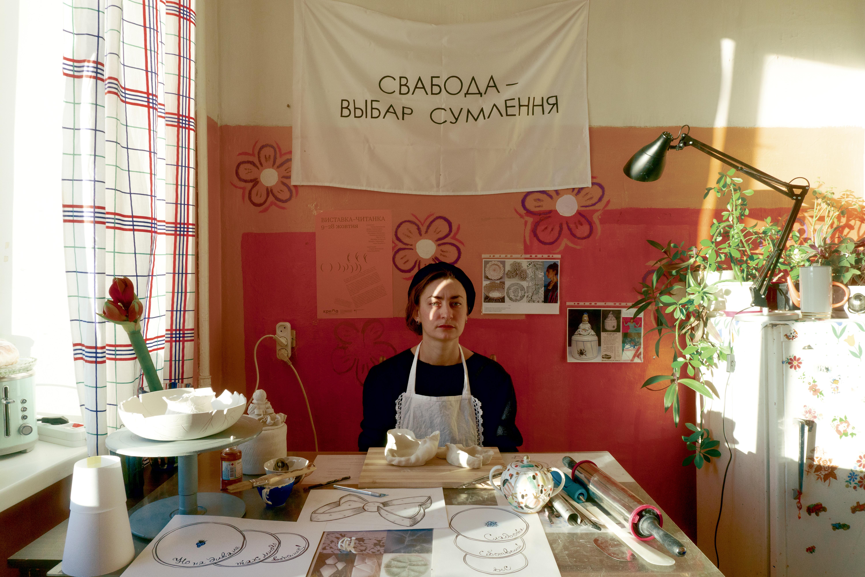Уляна Биченкова в майстерні, 2020. Фото: Поліна Полікарпова. (На стіні робота мінської художниці Олесі Житкевич)